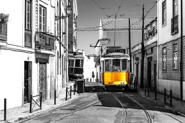 Yellow tram on old streets of Lisbon, Portugal, popular touristic attraction and destination. Black and white picture with a coloured tram. Wall mural