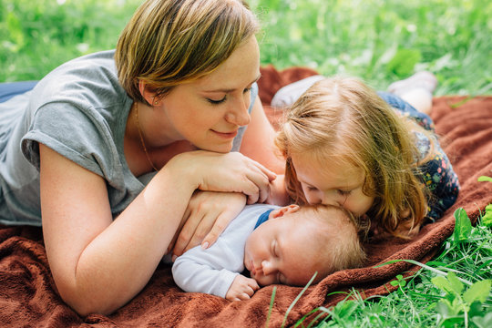 Young mom with her 4 years old daughter and 4 months old baby boy are relaxing and playing on blanket in the summer park