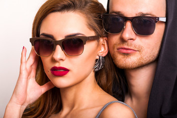 beautiful fashion couple with sunglasses on a white background. Vogue Style