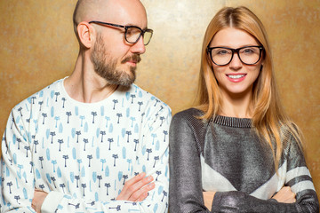 fashion hipster couple in love in glasses posing on a gold background. The concept of St. Valentine's Day..