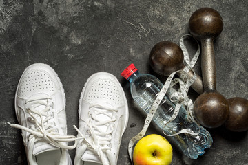 sports background top view of sneakers, dumbbells, bottle of water, apple and sentimeter tape on a black background with copy space. healthy lifestyle concept.