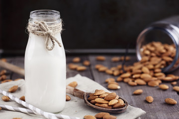 Organic white almond milk in a glass bottle with whole almonds spilled over a rustic wooden table.