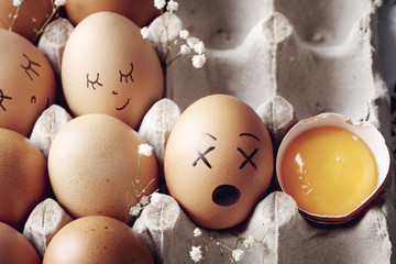 Emotional eggs in protective box with broken egg .