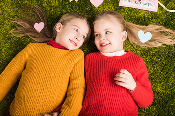 top view of adorable little sisters lying on carpet surrounded with hearts