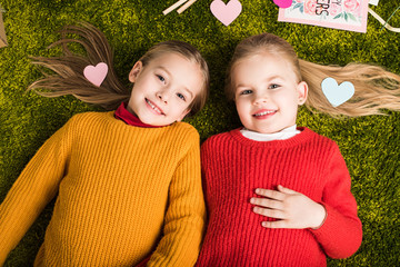 top view of happy little sisters lying on carpet surrounded with hearts