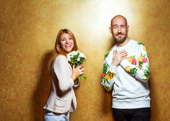 emotional fashion couple give each other flowers on Valentine's Day. Vogue style