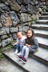 Beautiful, little girls are sitting on the steps in fashionable clothes. People, sisters, friends, relationships