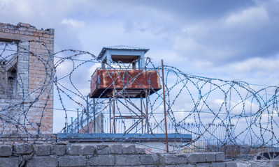 Historic brick prison wall showing guard tower and coiled barbed wire
