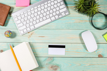 Top view office table and blank credit card on wood background.