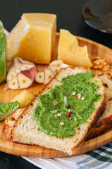Bruschetta with basil walnut pesto sauce on a wooden plate. Black stone backdrop.