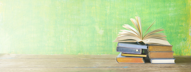open book on a stack of books,green grungy background, panoramic, good copy space