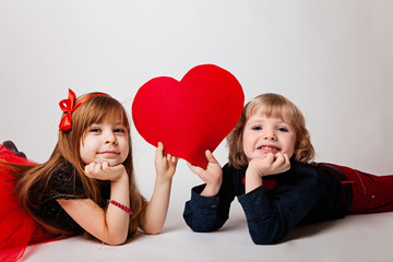 boy and girl lie holding a red heart