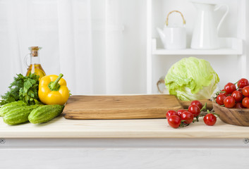 Kitchen table with vegetables and cutting board for preparing salad