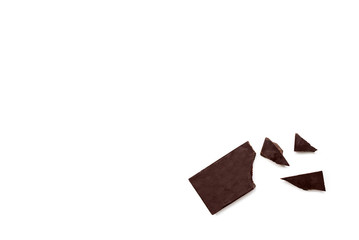 Broken dark chocolate bar isolated on white table. Horizontal composition. Top view