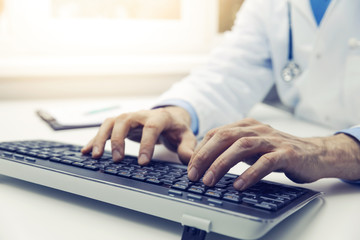doctor typing on computer keyboard in office. online consultation