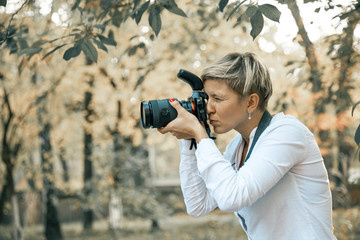 Professional woman photographer taking camera outdoor portraits with prime lens in the photography nature. Greenery tone
