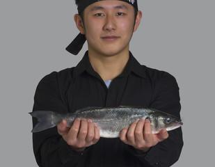 Cocinero asiatico sujetando un pez fresco para el sushi.