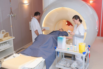 doctor looking at patient going through ct scan
