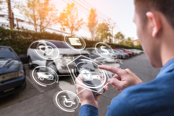The abstract image of business man point to the hologram on his smartphone and blurred garage is backdrop. the concept of communication, network, insurance, financial and internet of things.