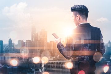 The double exposure image of the business man using a smartphone during sunrise overlay with cityscape image. The concept of modern life, business, city life and internet of things.