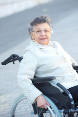 elderly disabled woman smiling in the street