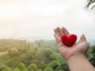 The hand holds the red heart.Forest, green trees and misty mountains. background copy space for text. Valentines day, love concept and love background