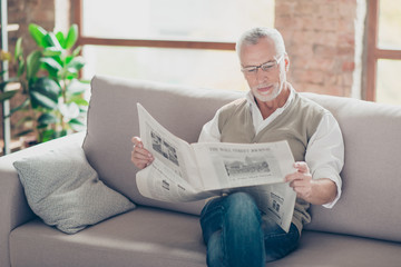 Calm careless atmosphere. Portrait of concentrated confident interested peaceful serious old granddad with white hair sitting on beige sofa with crossed legs reading favorite newspaper
