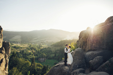 Romantic newlywed couple posing in sunset lights on majestic roc