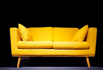 Yellow sofa in dark room with dim light background.