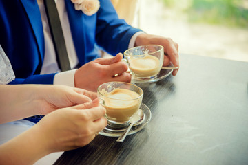two cups of cappuccino in the hands of a boy and a girl at a table in a cafe