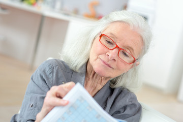elderly woman doing puzzles