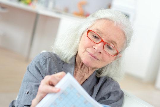 elderly woman doing puzzles
