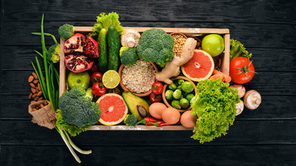 The concept of healthy food. Fresh vegetables, nuts and fruits in a wooden box. On a wooden...