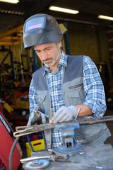 man welding steel outdoors