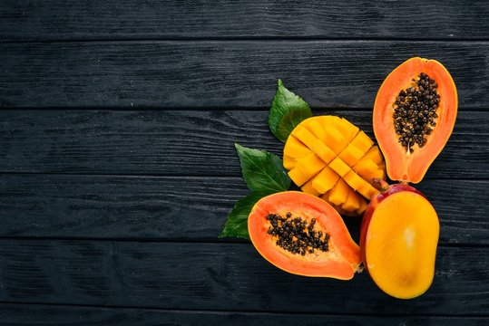 Mango and Papaya. Tropical Fruits. On a wooden background. Top view. Copy space.
