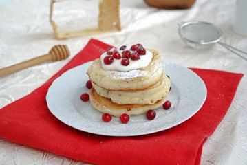 Berry pancakes with sour cream sauce and powdered sugar
