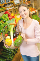 Lady holding wire basket of vegetables