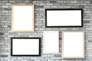 Different size and style empty photo frames on white concrete wall. with clipping path