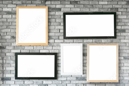Different size and style empty photo frames on white concrete wall ...