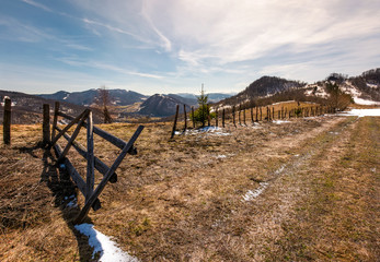 wooden fence on a hillside in springtime. beautiful landscape with grassy weathered slopes and some snow in mountains