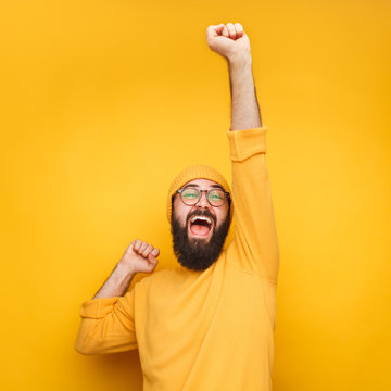 Celebrating bearded man with hand up