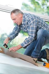 middle-age man assembles wood parts