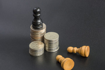 power of money concept. Black wooden chess pawn standing on coins, two white pawn fell, bowed