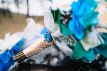 wedding bouquet of white and blue roses in hands of bride