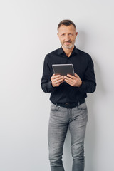 Relaxed man in jeans standing holding a tablet