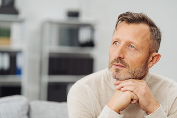 Middle-aged man sitting daydreaming