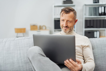 Man sitting using a laptop with a pleased smile