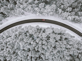 Drone aerial view of road in the snowy forest