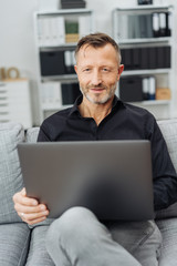 Man sitting at home browsing on a laptop