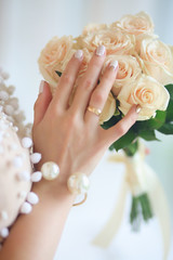 a bouquet of white roses in hands of bride